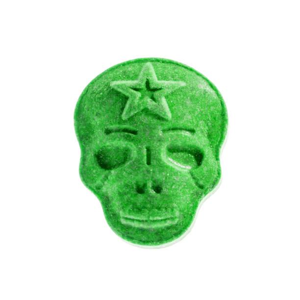 een groene xtc, ecstasy, mdma, amfetamine of medicijn pil in de vorm van een schedel geïsoleerd op een witte achtergrond. - amfetamine stockfoto's en -beelden