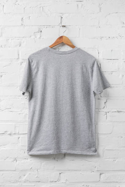 one grey shirt on hanger on white wall one grey shirt on hanger on white wall coathanger stock pictures, royalty-free photos & images