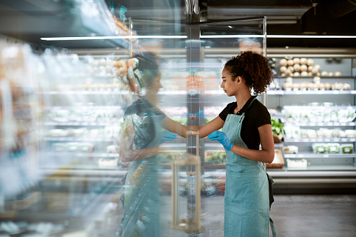 istock One grocery store employee adjusting products in the fridge. 1246318297