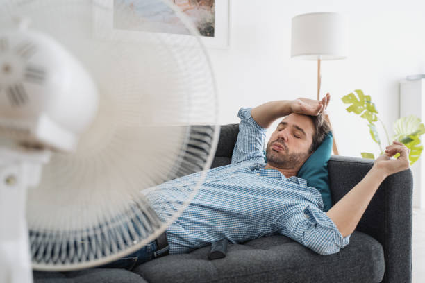 One guy portrait suffering from summer heat at home stock photo
