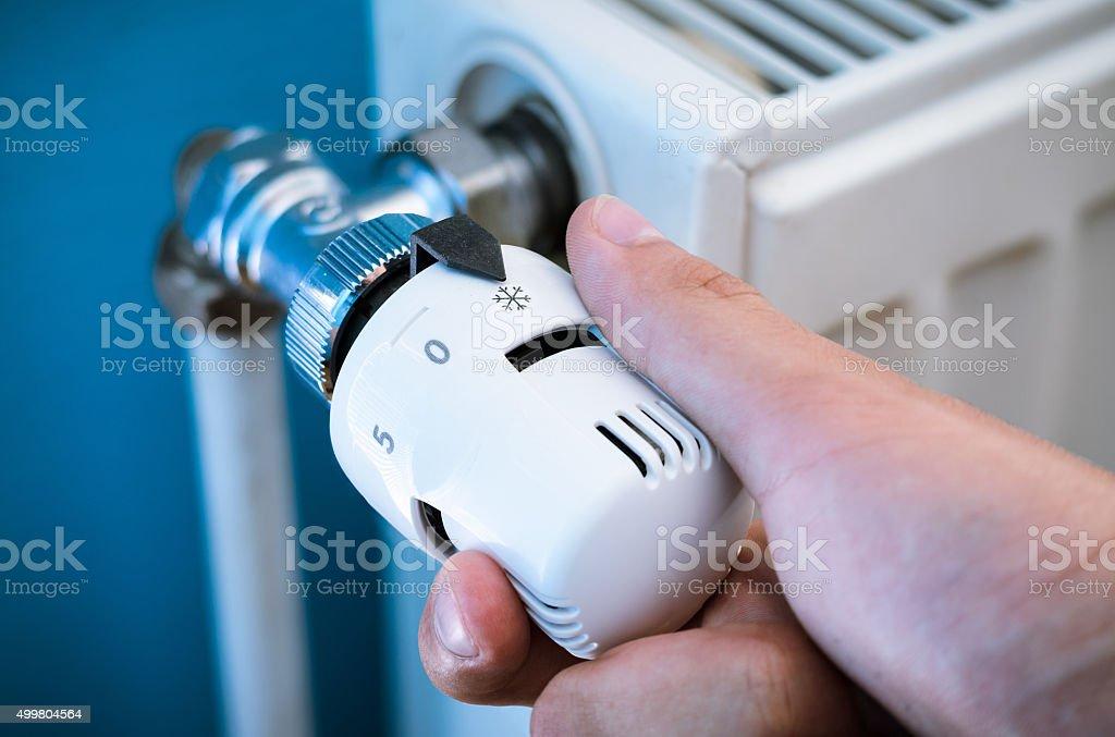 One hand adjust thermostat valve close up stock photo