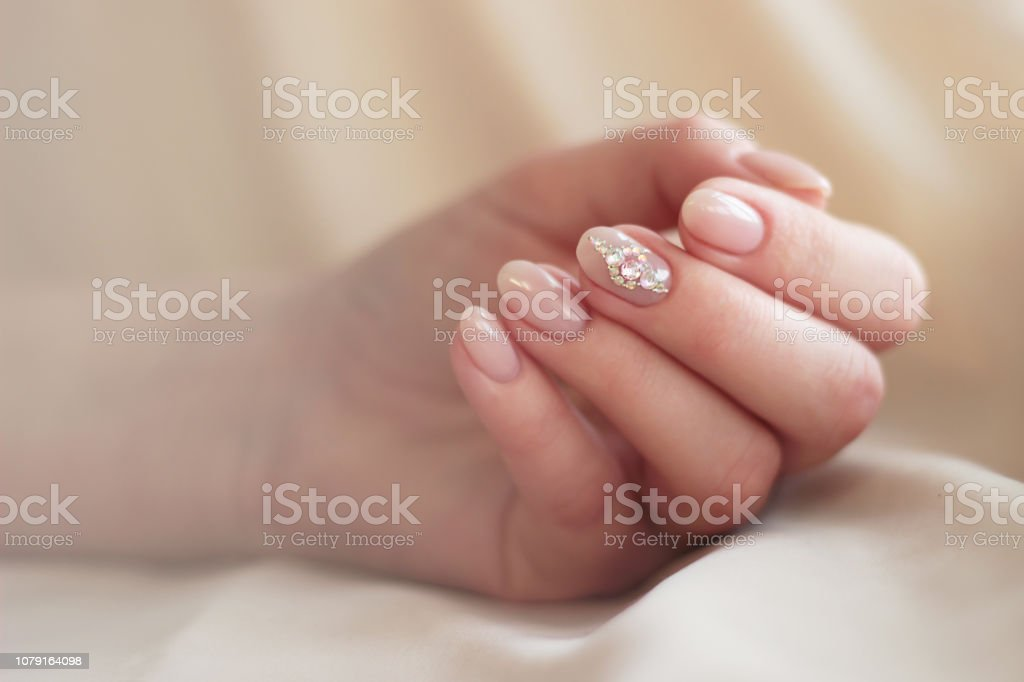 one hand gentle pink manicure with rhinestones on the middle finger