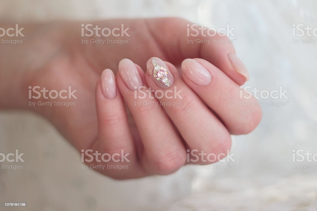 one hand gentle pink manicure with rhinestones on the middle finger...