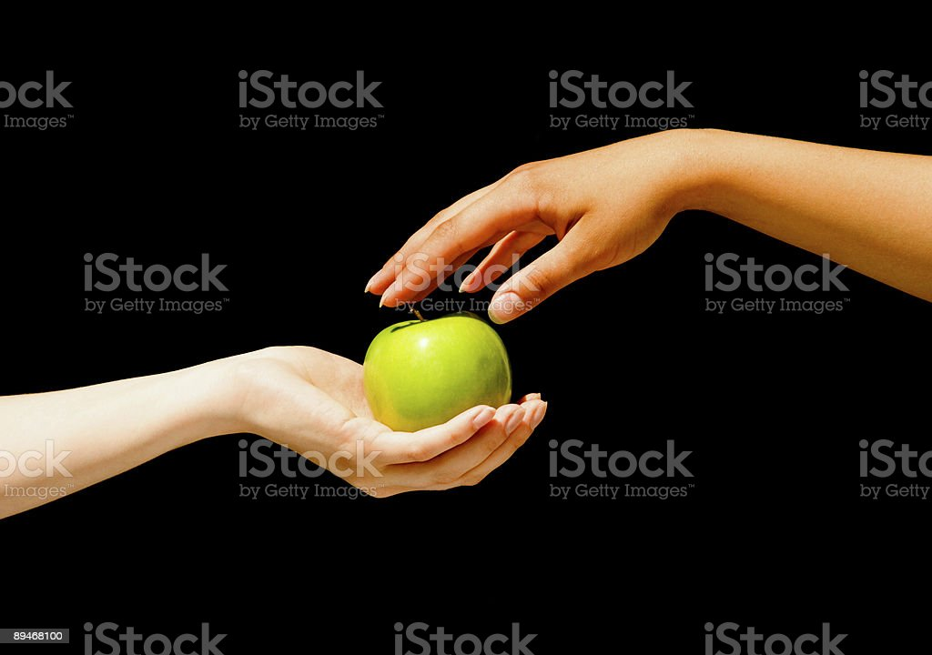 One hand giving a green apple to another royalty-free stock photo