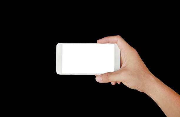 One hand holding mobile smartphone with white screen. Mobile photography concept. Isolated on black. stock photo