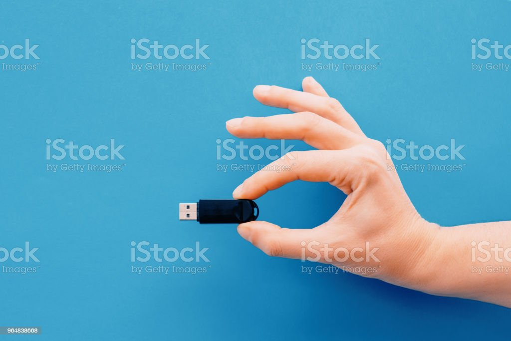 One hand holding pendrive on blue background stock photo
