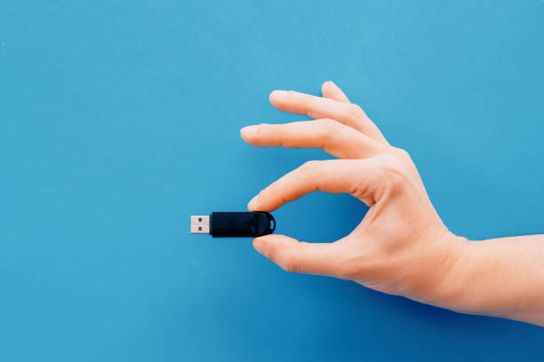 One hand holding pendrive on blue background Digital data memory concept.Hand holding pendrive on blue background usb stick stock pictures, royalty-free photos & images