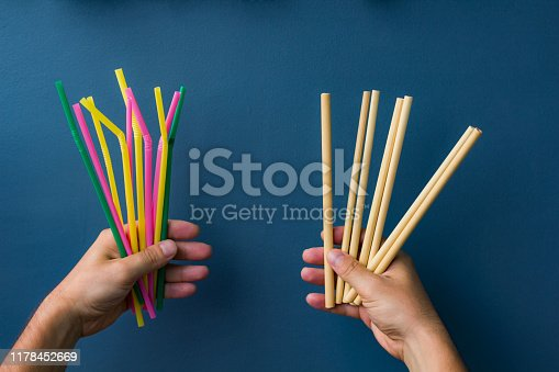 One hand holds colourful plastic straws and another hand holds bamboo straws. Good background for ecology topics