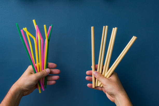 One hand holds colourful plastic straws and another hand holds bamboo straws. Good background for ecology topics One hand holds colourful plastic straws and another hand holds bamboo straws. Good background for ecology topics drinking straw stock pictures, royalty-free photos & images