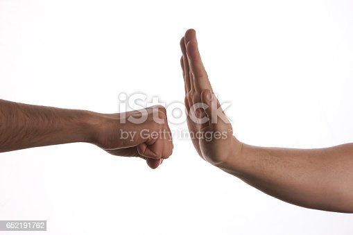 istock One hand preventing punch attack of another hand 652191762