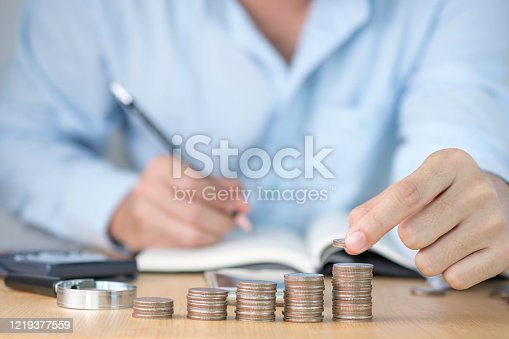 One hand putting coins stacking and one hand writing record for growth business and saving investment concept.
