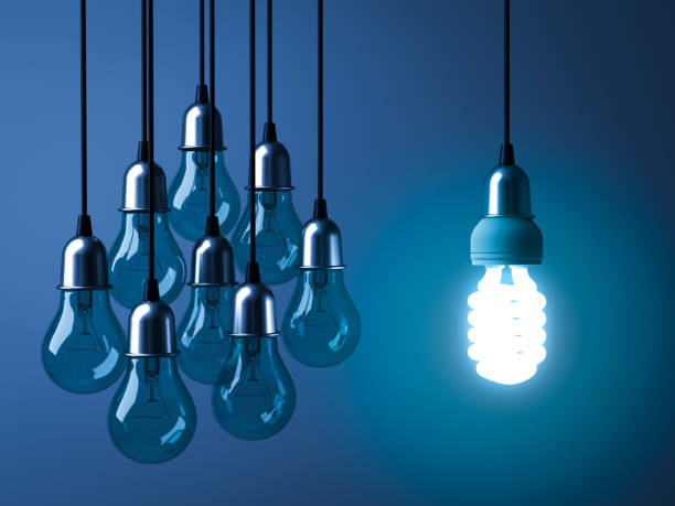 One hanging eco energy saving light bulb glowing and standing out from unlit incandescent bulbs on dark blue background One hanging eco energy saving light bulb glowing and standing out from unlit incandescent bulbs on dark blue background , leadership and different creative idea concept. 3D rendering. canadian football league stock pictures, royalty-free photos & images