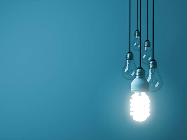 One hanging eco energy saving light bulb glowing and standing out from unlit incandescent bulbs on dark green pastel color background , leadership and different creative idea concept. 3D rendering stock photo