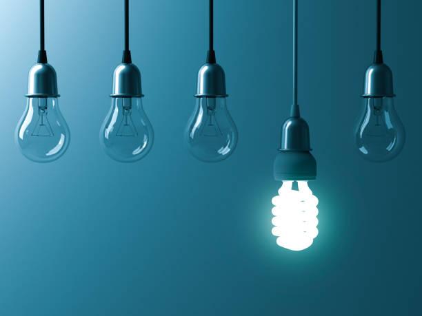Un colgante de ahorro bombilla que brilla intensamente diferentes sobresalen sin encender bombillas incandescentes con reflexión sobre fondo cian oscuro, liderazgo y representación 3D de la idea creativa diferente concepto - foto de stock