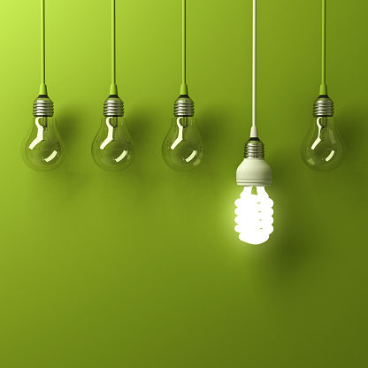 One hanging energy saving light bulb glowing different standing out from unlit incandescent bulbs with reflection on green background, leadership and different creative idea concept. 3D rendering.