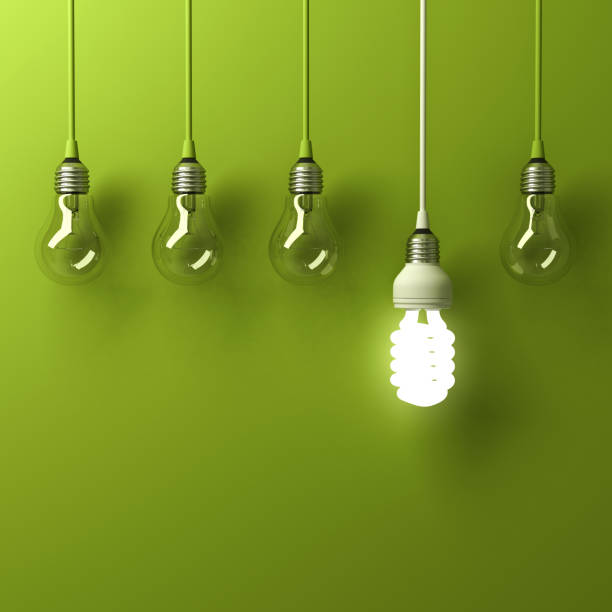 One hanging energy saving light bulb glowing different standing out from unlit incandescent bulbs with reflection on green background, leadership and different creative idea concept stock photo