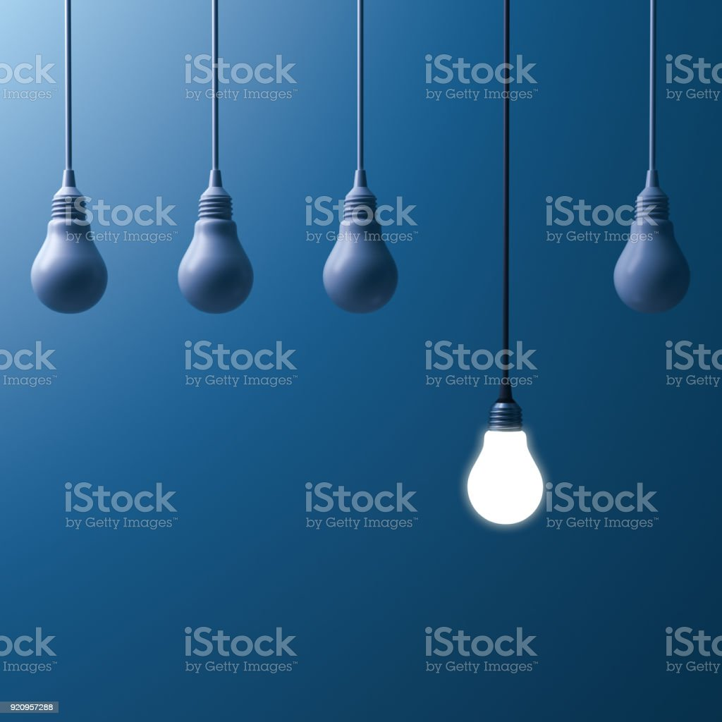 One hanging light bulb glowing and standing out from unlit...
