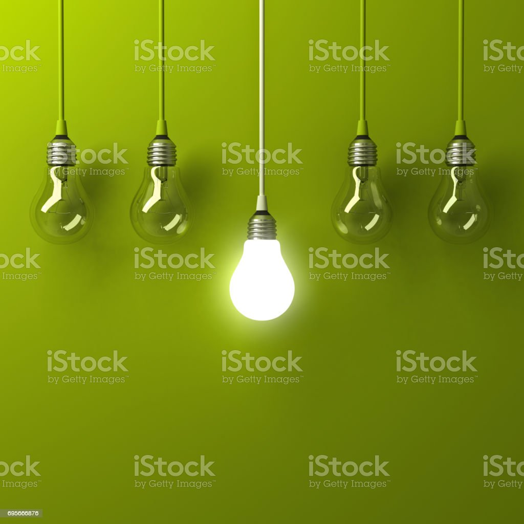 One hanging light bulb glowing different and standing out from unlit incandescent bulbs with reflection on green background , leadership and different business creative idea concept stock photo