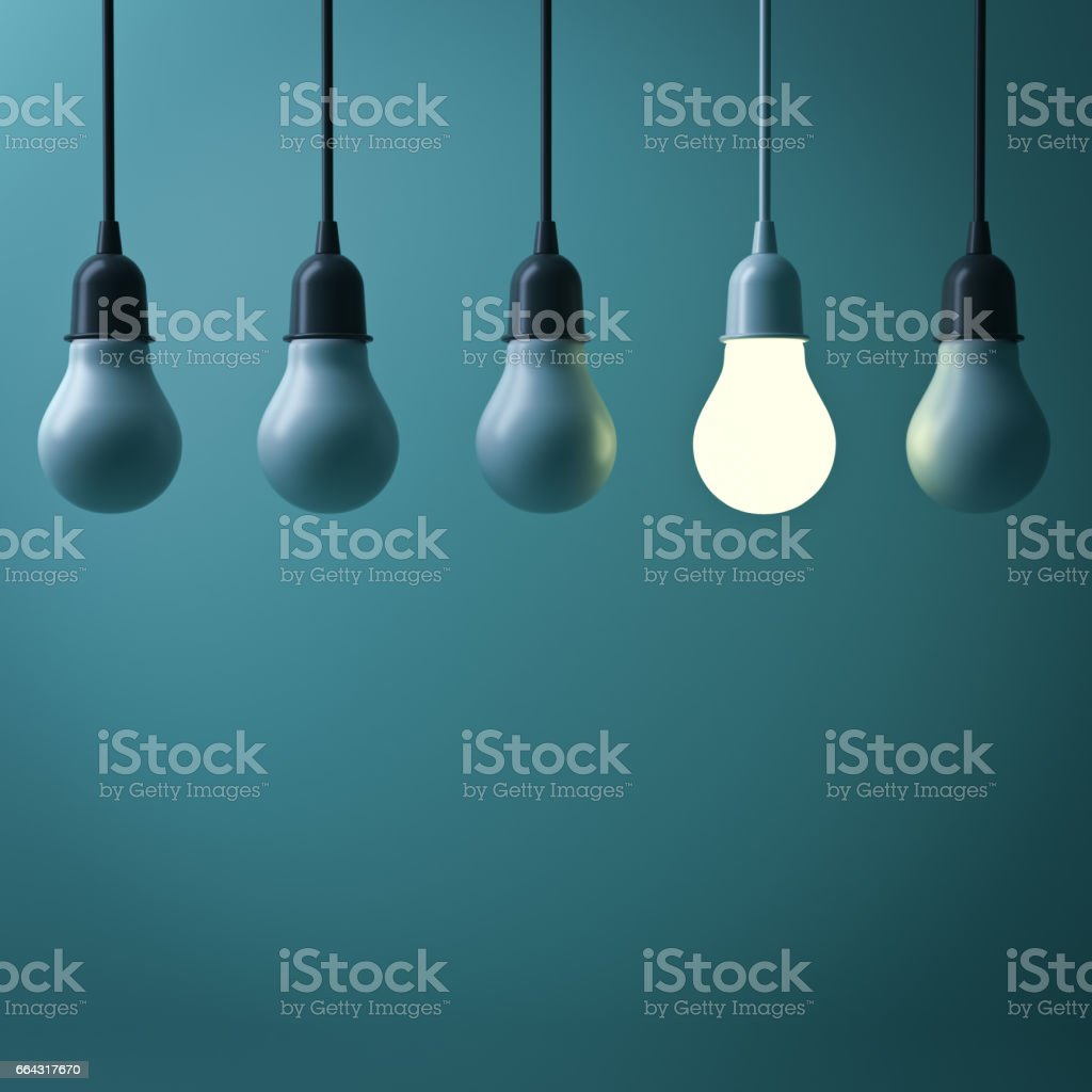 One hanging light bulb glowing different standing out from unlit incandescent bulbs with reflection on dark green background , leadership and different business creative idea concept. 3D render stock photo