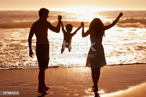 Rear-view of a couple swinging their child between them as they walk on the beach at sunset