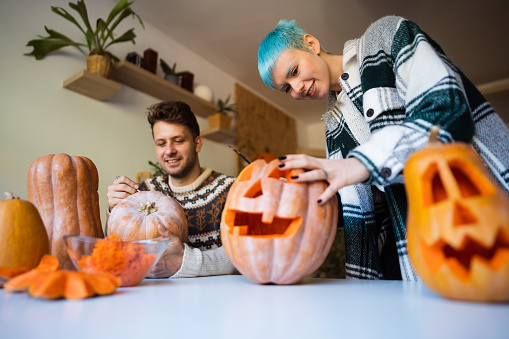 Young cheerful Caucasian couple preparing pumpkins for Halloween at home.