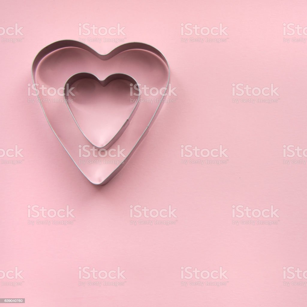 One heart shape cookie cutter within another on pink background. stock photo