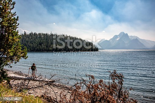 Jackson, United States - August 14, 2018:  One fifty year old man hiking along the banks of Jackson Lake in Grand Teton National Park on a warm summer afternoon.