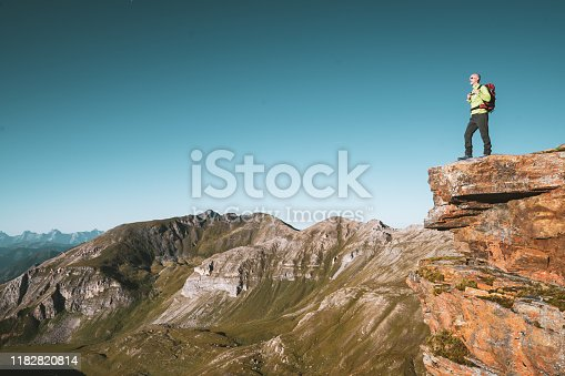 one mature adult 45 years old sporty hiking man with backpack standing on cliff high up in european mountains alps enjoying amazing view on sunny summer day with clear blue sky