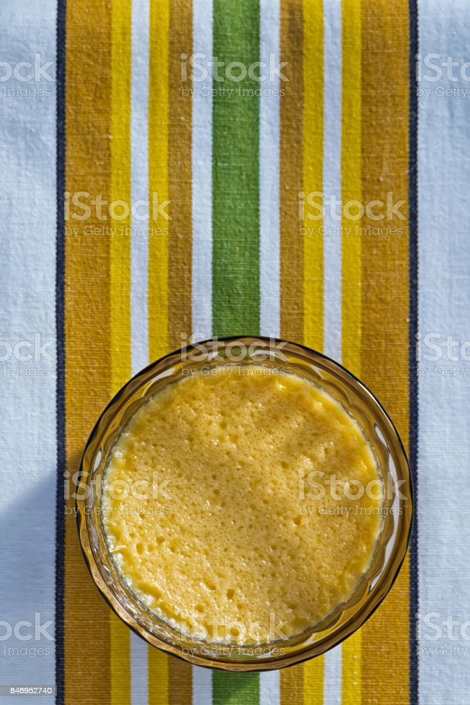 One Homemade Crème Brûlée on a stripy green stock photo
