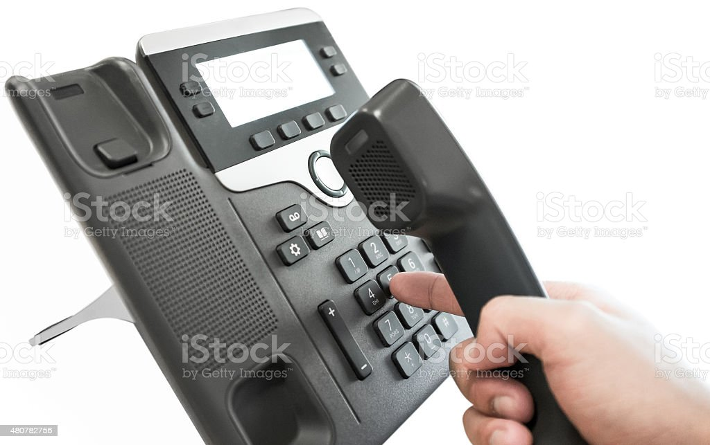 One human hand pressing key on telephone stock photo