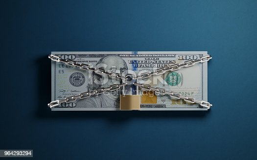 One hundred American dollar banknote tied with a padlock and chain on blue background. Security concept. Horizontal composition with selective focus and copy space.
