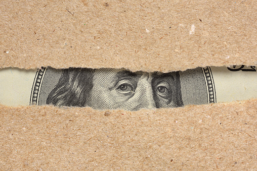 One hundred dollar bill Benjamin Franklin portrait looks behind brown craft ripped paper