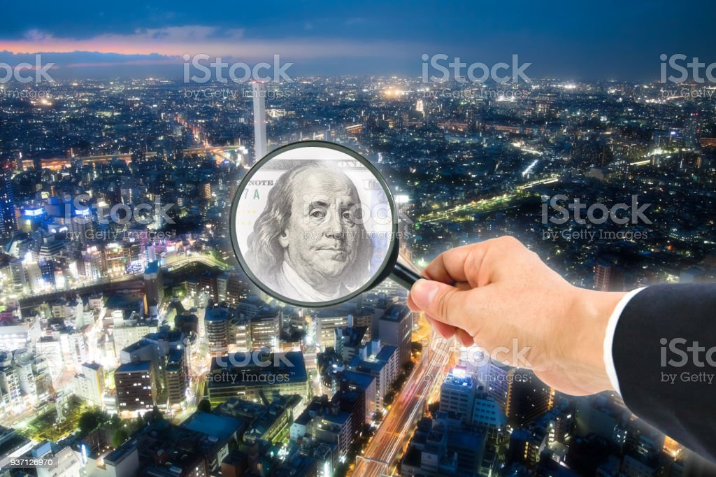 One hundred dollar bill in magnifying glass stock photo