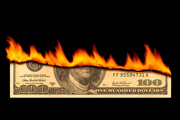 One hundred dollar bill on fire on black background Dollar note burning. money to burn stock pictures, royalty-free photos & images