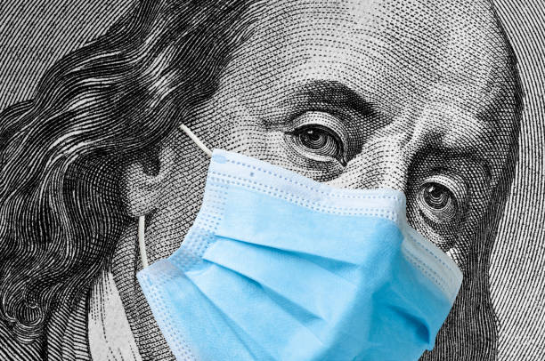 One hundred dollar bill with medical face mask on Benjamin Franklin. stock photo