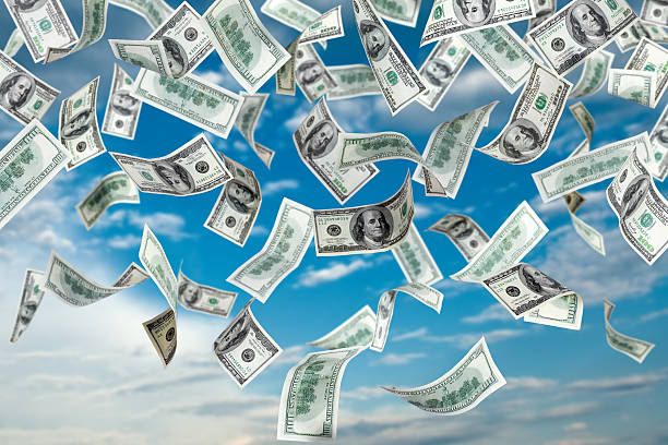 One hundred dollar bills falling out of the sky stock photo