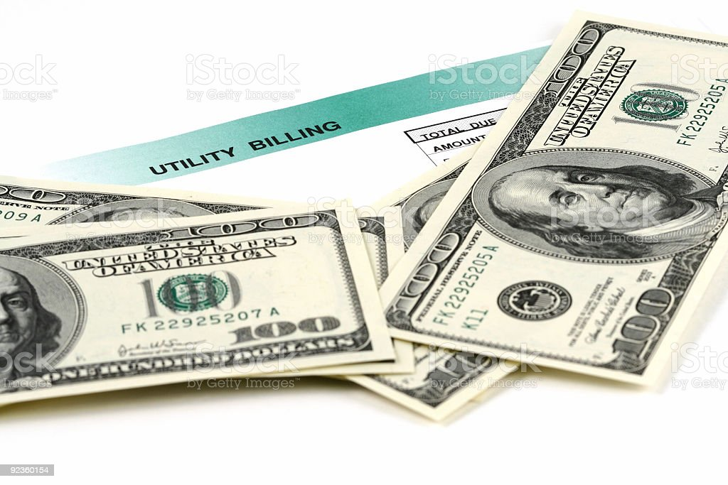 One hundred dollar bills laying on top of a utility bill royalty-free stock photo