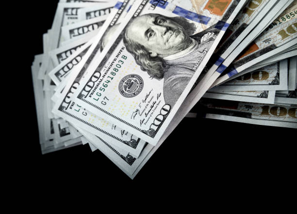 one hundred dollars isolated on black background - money black background stock photos and pictures