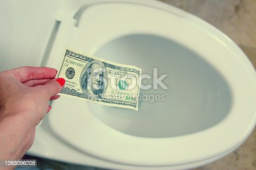 istock One hundred paper dollars in a female hand. 1263096205
