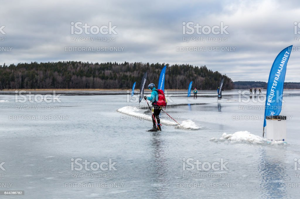 One ice skater on a wet frozen ice course with flags. stock photo