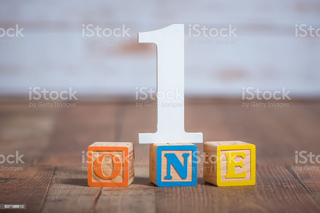 One in the number and wooden blocks spelled out – Foto