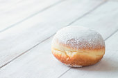 One jelly filled doughnut with powdered sugar