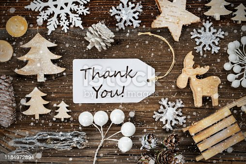 White Label With English Text Thank You. Frame Of Christmas Decoration Like Tree, Sled, Star And Fir Cone. Wooden Background With Snowflakes