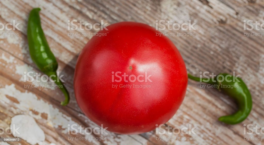 One large organic ripe tomato and two sharp green chili royalty-free stock photo