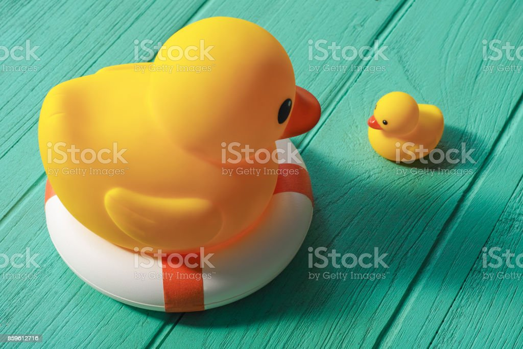 One large yellow rubber duck on a safety inflatable life ring facing a little yellow rubber duck with no life ring. wooden table background. stock photo