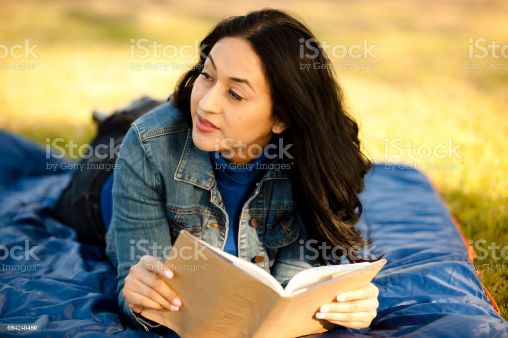 One Latin descent woman reading outdoors in park. royalty-free stock photo