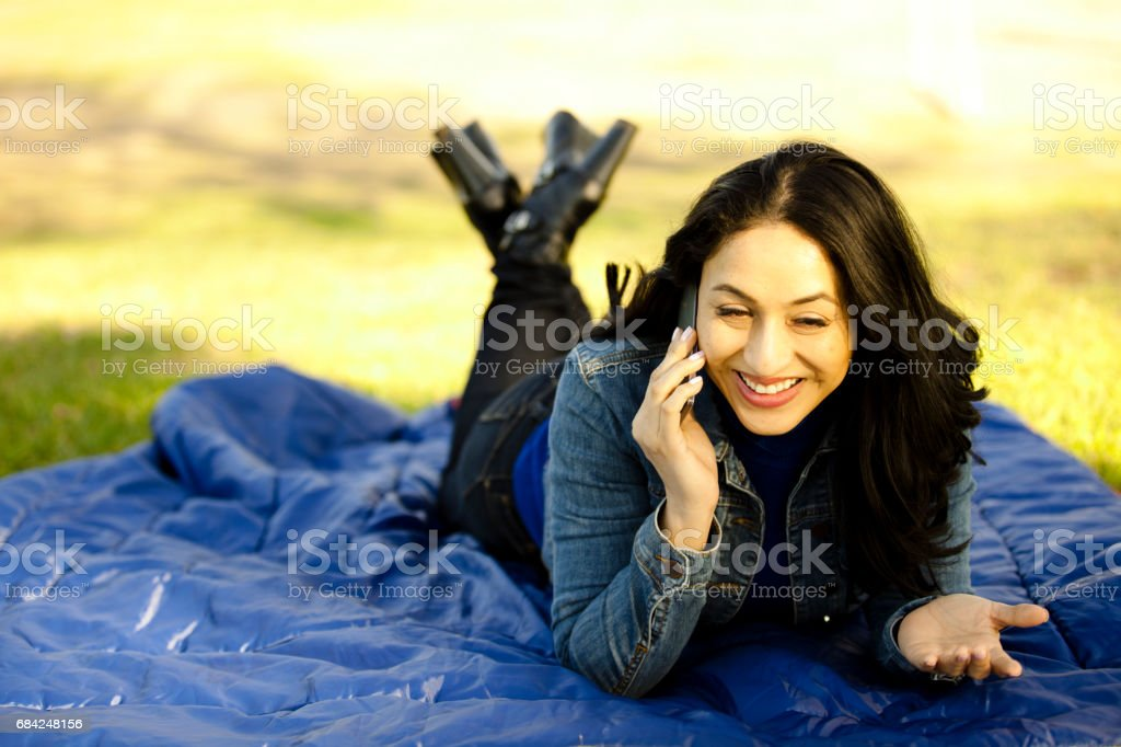 One Latin descent woman using cell phone outdoors in park. royalty-free stock photo