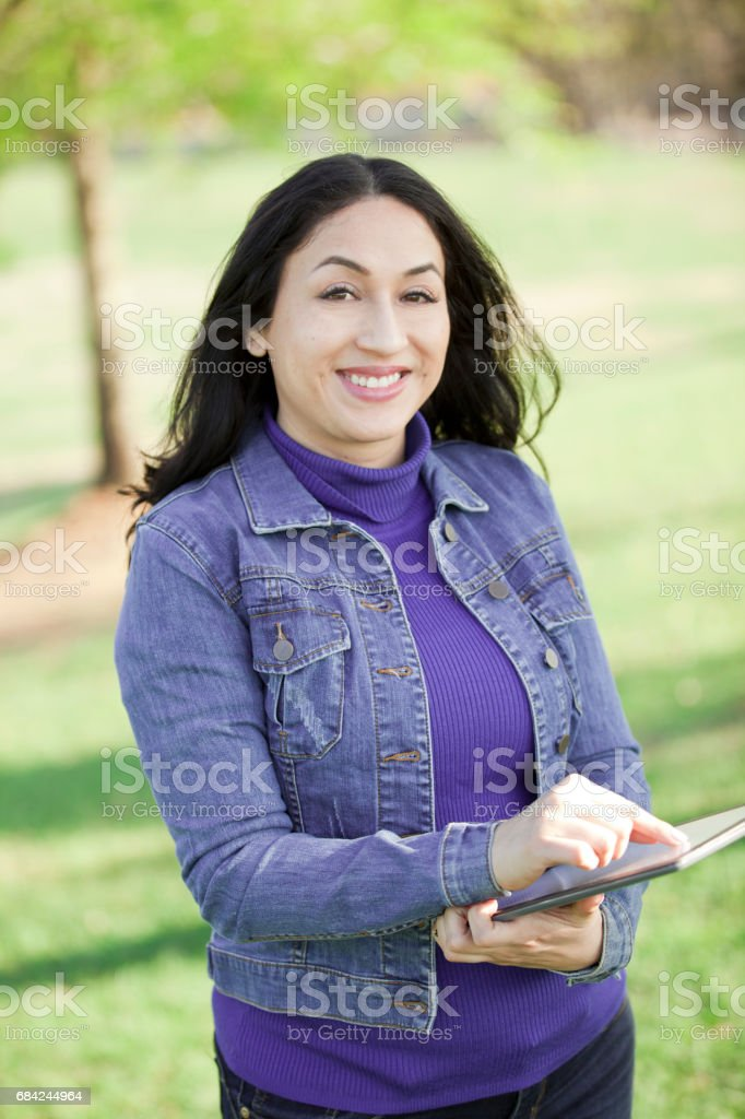 One Latin descent woman using digital tablet outdoors in park. royalty-free stock photo