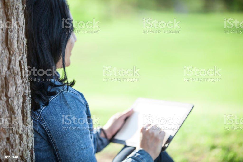 Une femme d'origine latine à l'aide de la tablette numérique à l'extérieur dans le parc. photo libre de droits