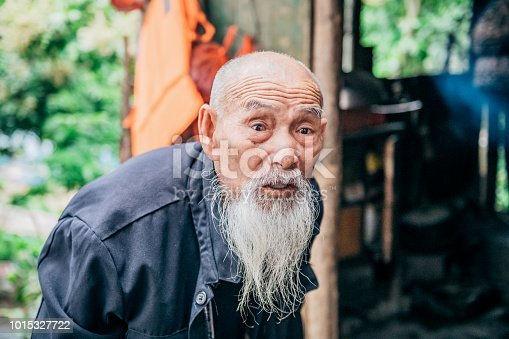 old frail chinese senior man in front of simple hut